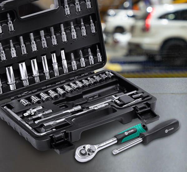 Maleta do kit de ferramentas está aberta sobre uma mesa, junto com mais duas ferramentas que estão fora da maleta.