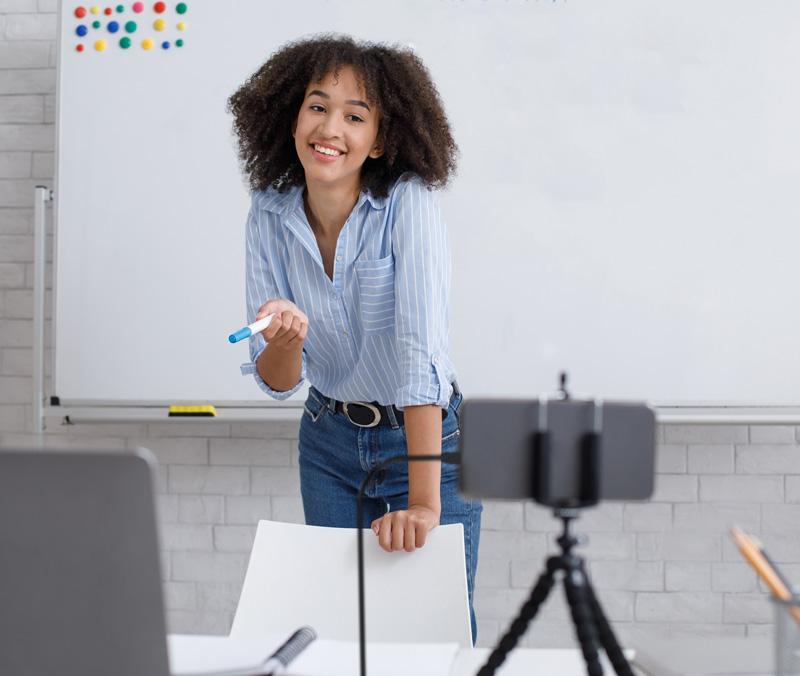 Mulher negra transmitindo aula ao vivo através do celular através da placa de captura