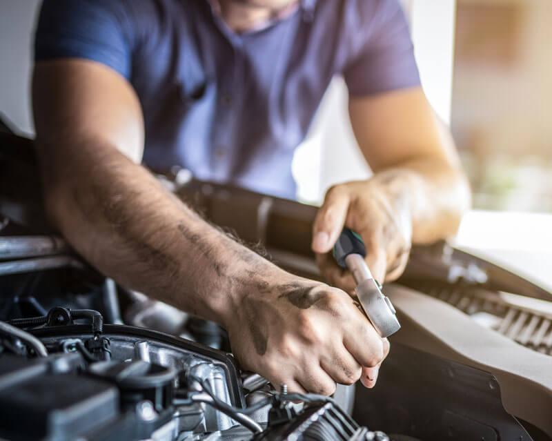Homem mexendo em motor de carro