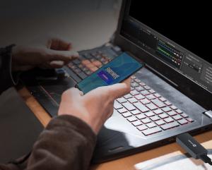 Pessoa jogando Fortnite pelo celular. O celular está conectado ao notebook através da placa de captura portátil