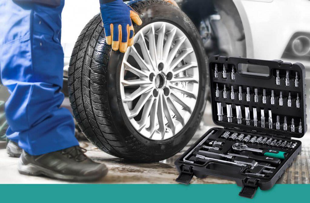 Caixa de Ferramentas VINIK ao lado de um homem trocando o pneu de um carro na oficina